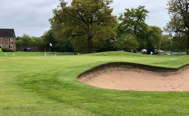 A view of a green protected by a huge bunker at Forest of Galtres Golf Club.