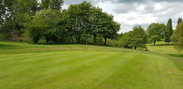 A sunny day view of a hole at Queens Park Golf Club.